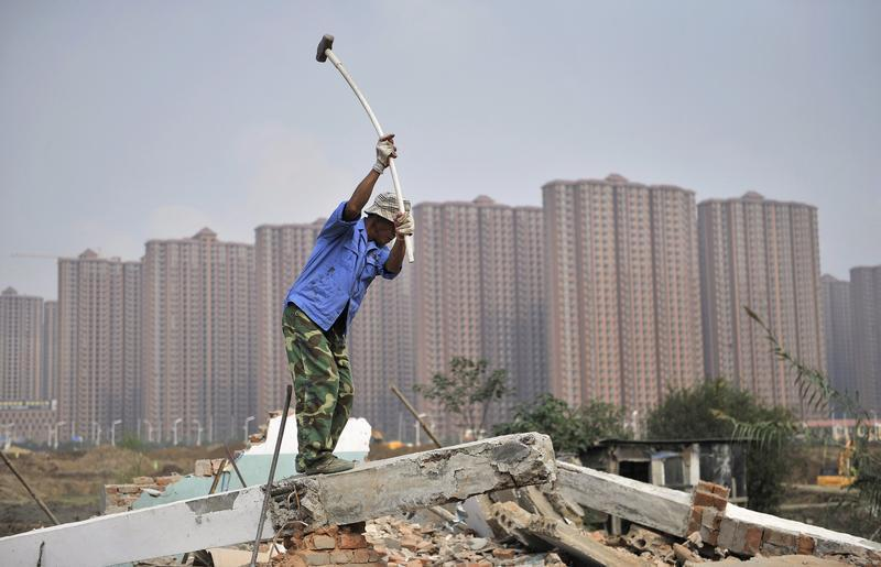 A worker wields a hammer at a demolition site in front of new residential buildings in Hefei, Anhui province