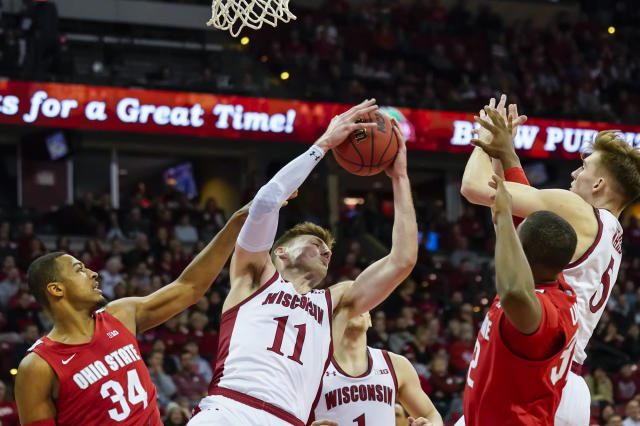 Wisconsin's Micah Potter (11) grabs a defensive rebound against Ohio State's Kaleb Wesson (34) and E.J. Liddell, second from right, during the first half of an NCAA college basketball game Sunday, Feb. 9, 2020, in Madison, Wis. (AP Photo/Andy Manis)