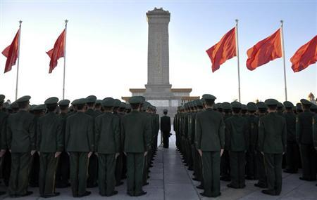 Paramilitary policemen stand in formation as they pay tribute to the Monument to the People's Heroes on Tiananmen Square in Beijing