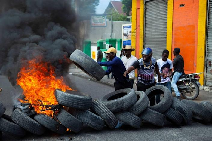 Protesters throw wheels onto a burning barricade during a demonstration demanding the resignation of President Jovenel Moïse, in Port-au-Prince, Haiti, Friday, Jan. 15, 2021.