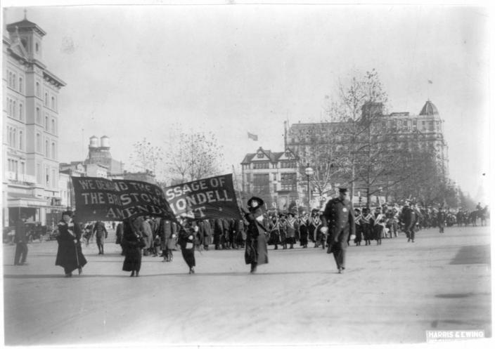 "In this photo provided by the Library of Congress, taken in 1913, four women march ahead of large procession with the banner ""We demand the passage of the Bristow-Mondell amendment"" at the woman suffrage parade in Washington. Thousands of women take to the streets of Washington, demanding a greater voice for women in American political life as a new president takes power. This will happen on Saturday, Jan. 21, 2017, one day after the inauguration of Donald Trump. This DID happen more than 100 years ago, one day before the inauguration of Woodrow Wilson. (Library of Congress via AP)"