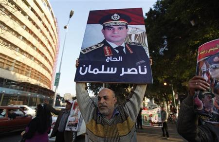Anti-Mursi protester carries a poster of Egypt's army chief Abdel Fattah al-Sisi during a protest supporting al- Sisi in front of the state television building, central Cairo