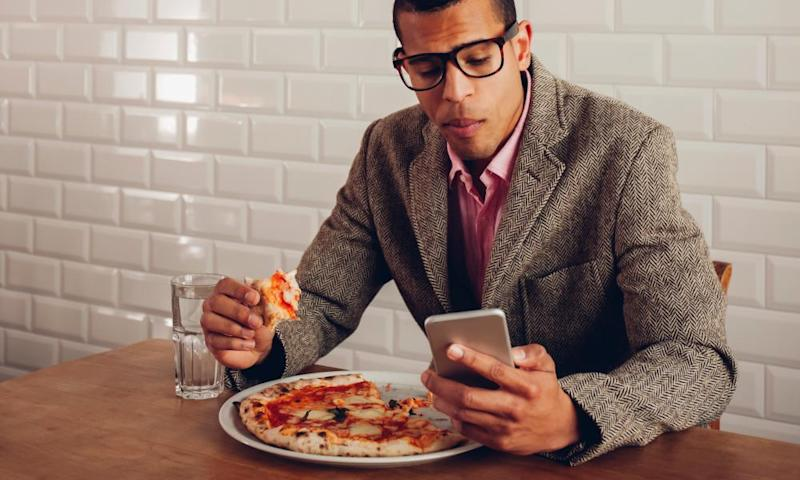 Man eating pizza alone looking at mobile