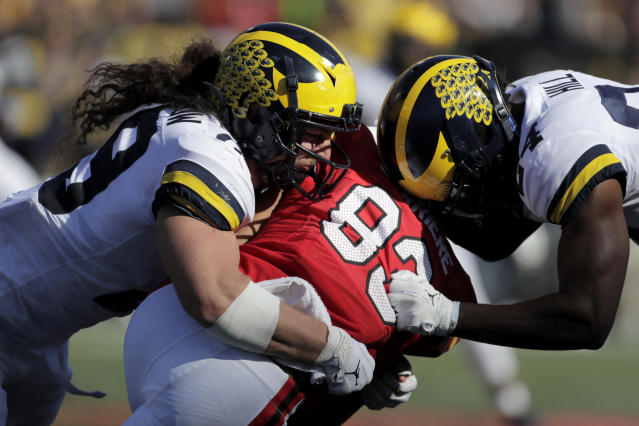 Maryland wide receiver Carlos Carriere, center, is tackled by Michigan linebacker Jordan Glasgow, left, and defensive back Lavert Hill during the second half of an NCAA college football game, Saturday, Nov. 2, 2019, in College Park, Md. Michigan won 38-7. (AP Photo/Julio Cortez)