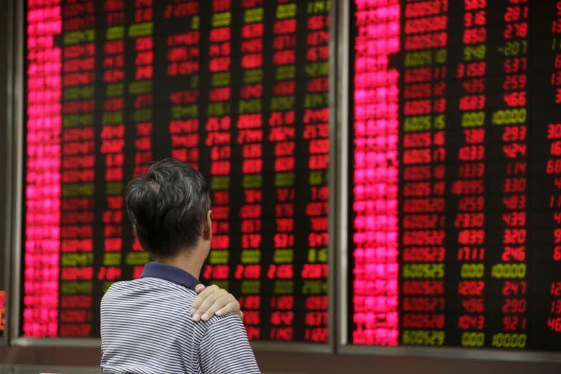 FILE PHOTO: An investor looks at an electronic board at a brokerage house in Beijing