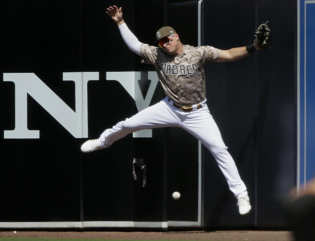 San Diego Padres right fielder Hunter Renfroe leaps for but misses the ball for a triple by Arizona Diamondbacks' Nick Ahmed during the second inning of a baseball game in San Diego, Sunday, Sept. 22, 2019. (AP Photo/Alex Gallardo)