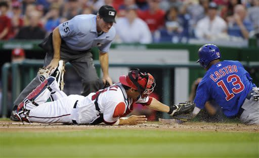 Chicago Cubs' Starlin Castro (13) is out at home after a tag by Washington Nationals catcher Kurt Suzuki, left, during the third inning of a baseball game, Friday, May 10, 2013, in Washington. Home plate umpire Angel Hernandez waits to make the call. (AP Photo/Nick Wass)