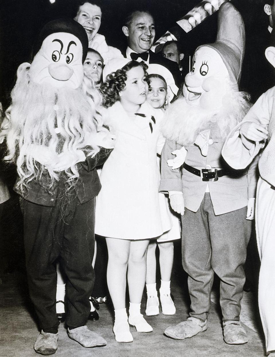 <p>Child star Shirley Temple poses with costumed dwarfs at the Hollywood film premiere of Disney's S<em>now White and the Seven Dwarfs</em> on December 23, 1937.</p>