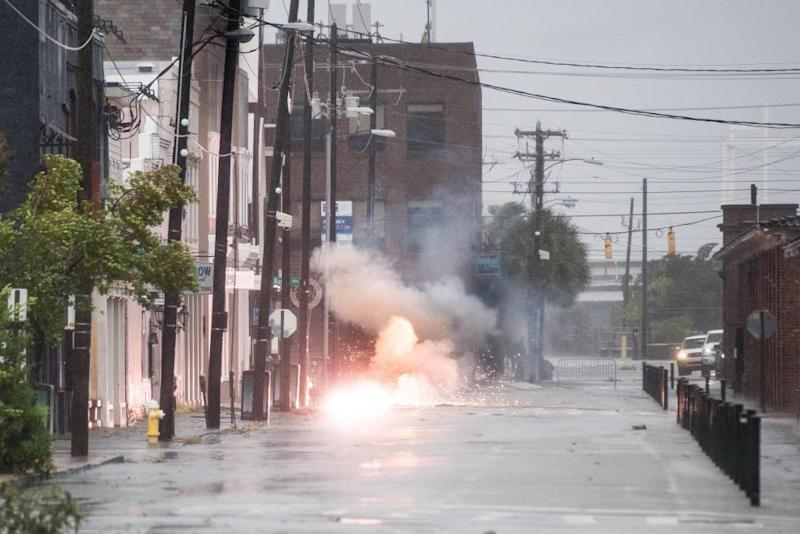 Power lines spark in flood water on Market Street as Hurricane Dorian spins just off shore on 5 September 2019 in Charleston, South Carolina.