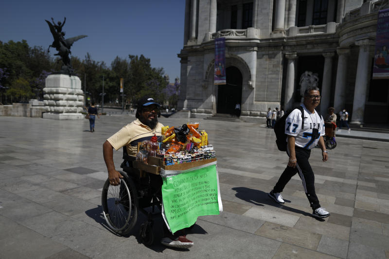 Guillermo Gonzalez Sanchez sells cigarettes and snacks from atop his wheelchair, outside the Palace of Fine Arts in downtown Mexico City, Tuesday, March 24, 2020. Gonzalez, who doesn't believe the new coronavirus is real, says the threat is just the latest tactic to suppress the Mexican people, many of whom like him live from day to day. (AP Photo/Rebecca Blackwell)
