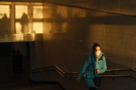 A woman wearing a face mask to help curb the spread of the coronavirus walks from the underpass up to the street during sunset in Moscow, Russia, Wednesday, Dec. 2, 2020. Russia has registered a record number of coronavirus deaths for a second straight day. Currently, there is a country-wide mask mandate and mostly mild restrictions that vary from region to region. (AP Photo/Alexander Zemlianichenko)