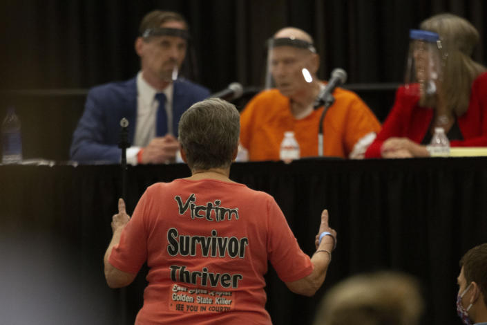 Jane Carson-Sandler, a 1976 rape victim of Golden State Killer Joseph James DeAngelo, stands and gives a double thumbs -up to agree with a prosecutor's statement about part of DeAngelo's anatomy, during a court hearing in Sacramento, Calif., Monday, June 29, 2020. DeAngelo, 74, pleaded guilty to 13 counts of murder and multiple other charges 40 years after a sadistic series of assaults and slayings in California. Due to the large numbers of people attending, the hearing was held at a ballroom at Sacramento State University to allow for social distancing. (AP Photo/Rich Pedroncelli)