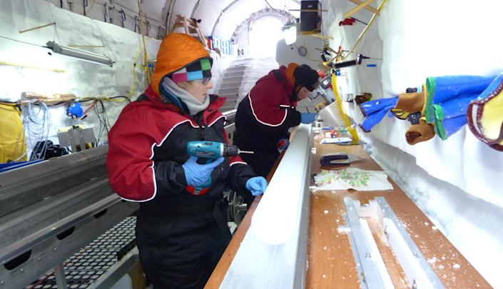 In this Nov. 22, 2012 photo released by scientist Nancy Bertler, doctoral students, Holly Winton, left, and Aja Ellis, work on an ice core on Roosevelt Island, Antarctica. The continent's pristine habitat provides a laboratory for scientists studying the effects of climate change. (AP Photo/Nancy Bertler)