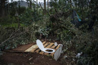 A makeshift toilet is pictured with a toilet seat on a pallet covering a hole in the ground outside Las Raices camp in San Cristobal de la Laguna, in the Canary Island of Tenerife, Spain, Sunday, March 21, 2021. While Spain has been critical of its European neighbours' lack of solidarity when it comes to sharing the responsibility of migration, the country is similarly being criticized by migrants, authorities and human rights organizations on the Canary Islands where some 23,000 people arrived by sea last year and where many thousands remain on the island forcefully. (AP Photo/Joan Mateu)