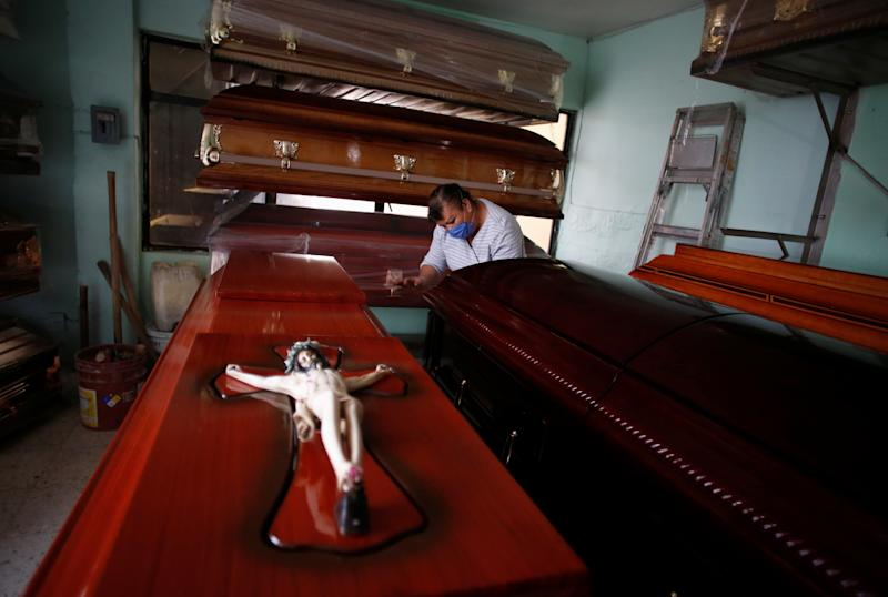 An employee cleans coffins at the Ermita funeral home amid the coronavirus disease (COVID-19) outbreak in Mexico City, Mexico May 9, 2020. Picture taken May 9, 2020. REUTERS/Gustavo Graf