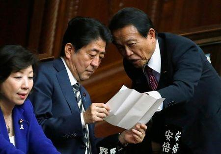 Japan's PM Abe talks with DPM and Finance Minister Aso at the Lower House of the Parliament in Tokyo