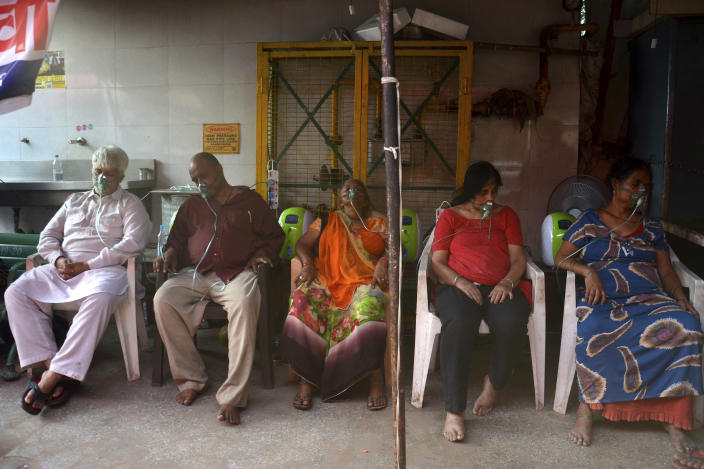 COVID-19 patients receive oxygen outside a Gurdwara, a Sikh house of worship, in New Delhi, India, Saturday, May 1, 2021. India on Saturday set yet another daily global record with 401,993 new cases, taking its tally to more than 19.1 million. Another 3,523 people died in the past 24 hours, raising the overall fatalities to 211,853, according to the Health Ministry. Experts believe both figures are an undercount. (AP Photo/Amit Sharma)