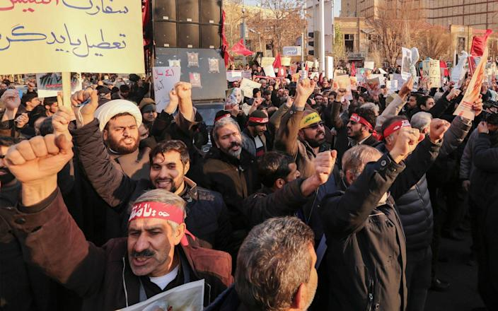 Iranian demonstrators hold placards and chant anti-Britain slogans in front of the British embassy in the capital Tehran on January 12 - AFP