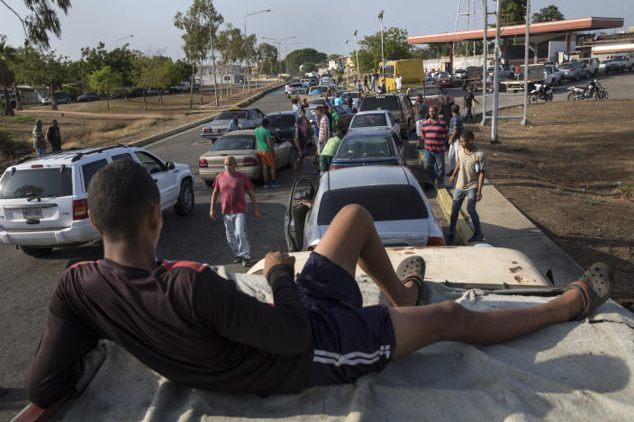 People line the street with their vehicles as they wait to fill up with gas at a fuel station, top right, in Cabimas, Venezuela, Wednesday, May 15, 2019. U.S. sanctions on oil-rich Venezuela appear to be taking hold, resulting in mile-long lines for fuel in the South American nation's second-largest city, Maracaibo. (AP Photo/Rodrigo Abd)
