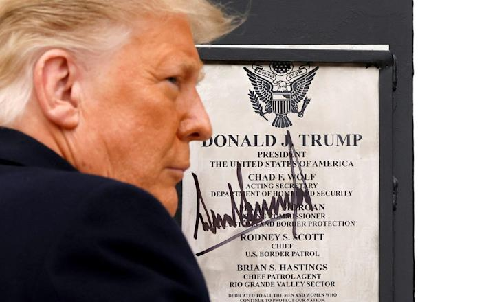 U.S. President Donald Trump signs a plaque placed at the U.S.-Mexico border wall during his visit, in Alamo, Texas - Carlos Barria/Reuters
