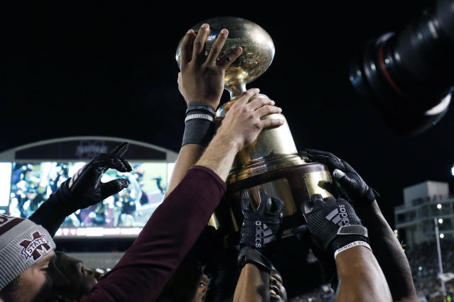 "Mississippi State players reach for the ""Egg Bowl"" trophy after defeating in-state rival Mississippi in an NCAA college football game in Starkville, Miss., Thursday, Nov. 28, 2019. (AP Photo/Rogelio V. Solis)"