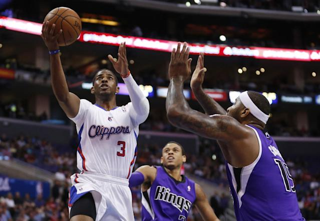 CORRECTS DAY OF WEEK TO SATURDAY - Los Angeles Clippers guard Chris Paul shoots the ball in front of Sacramento Kings guard Ray McCallum, center, and Kings center DeMarcus Cousins, right, during the first half of an NBA basketball game in Los Angeles, Saturday, April 12, 2014. (AP Photo/Danny Moloshok)