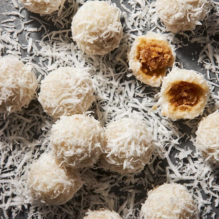 """<p>This recipe for traditional Thai coconut balls is all about the coconut. First, skip the preshredded stuff (the filling won't hold together with it) and get yourself to the produce department for a fresh one. Look for a coconut with a brown husk (rather than one with a white fibrous exterior, often labeled """"young Thai"""" coconut). Brown-husked coconuts have firmer flesh that's easier to shred.</p>"""