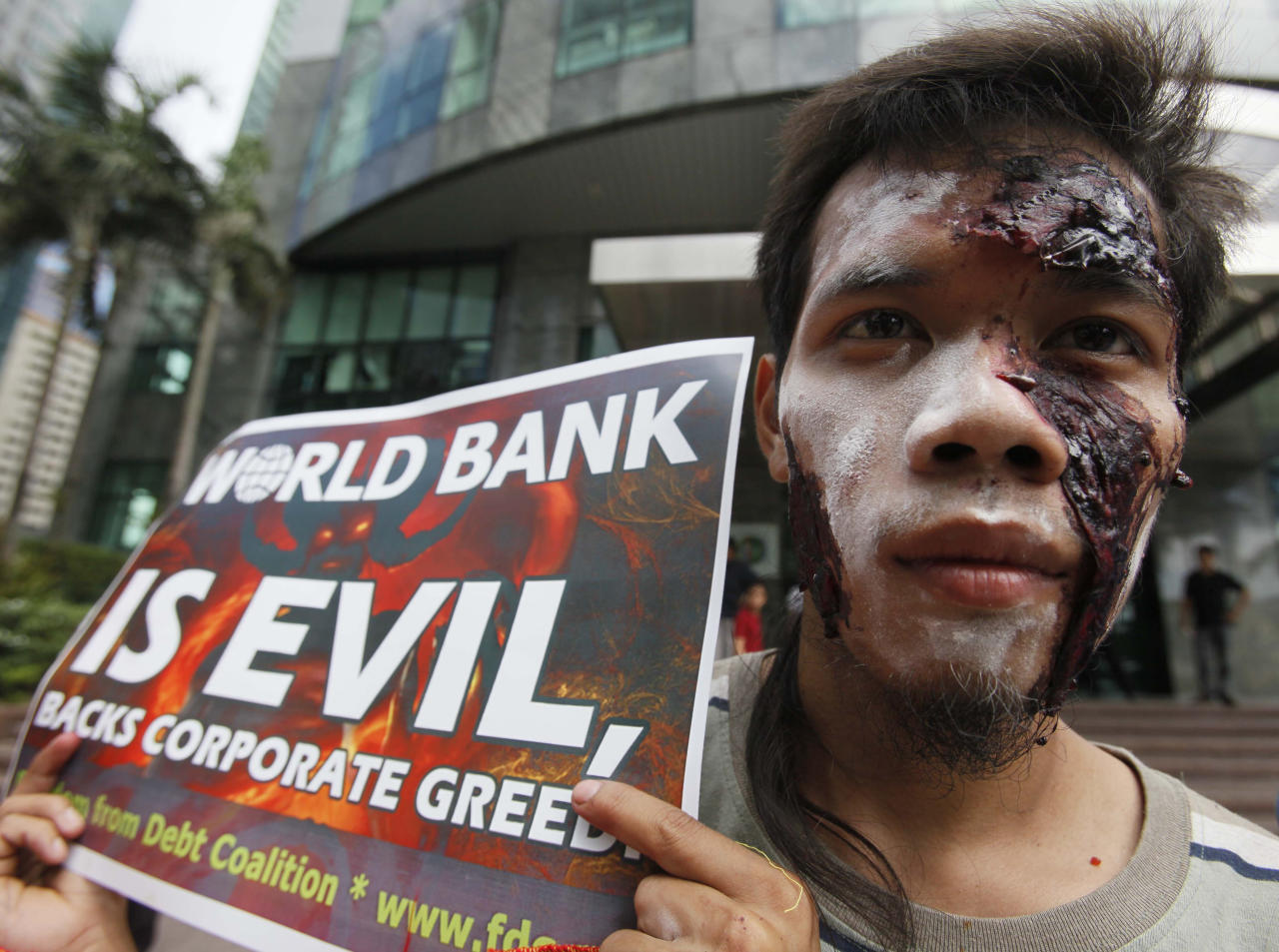 A protester, sporting his Halloween costume and makeup, displays a placard as they picket the World Bank office Thursday Oct. 27, 2011 where visiting World Bank President Robert Zoellick is holding a news conference at suburban Mandaluyong, east of Manila, Philippines. Zoellick welcomed a deal clinched by European leaders to address their two-year debt crisis, saying it may have helped avert the spread of the financial turmoil to emerging markets that provide half of global economic growth. (AP Photo/Bullit Marquez)