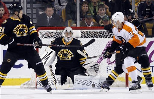 Philadelphia Flyers' Matt Read (24) flips the puck into the net past Boston Bruins' Tim Thomas, center, as the Bruins' Andrew Ference (21) looks on in the second period of an NHL hockey game in Boston, Saturday, March 17, 2012. (AP Photo/Michael Dwyer)
