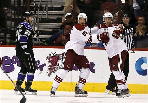 Phoenix Coyotes' Shane Doan, right, celebrates his goal with teammate Antoine Vermette as Los Angeles Kings' Slava Voynov (26), of Russia, skates past in the first period during an NHL hockey game Tuesday, March 12, 2013, in Glendale, Ariz. (AP Photo/Ross D. Franklin)