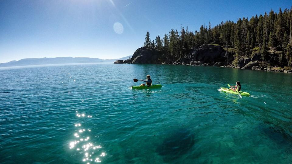 Children kayak and play in the beautiful clear waters of Lake Tahoe, California on a beautiful summer morning.