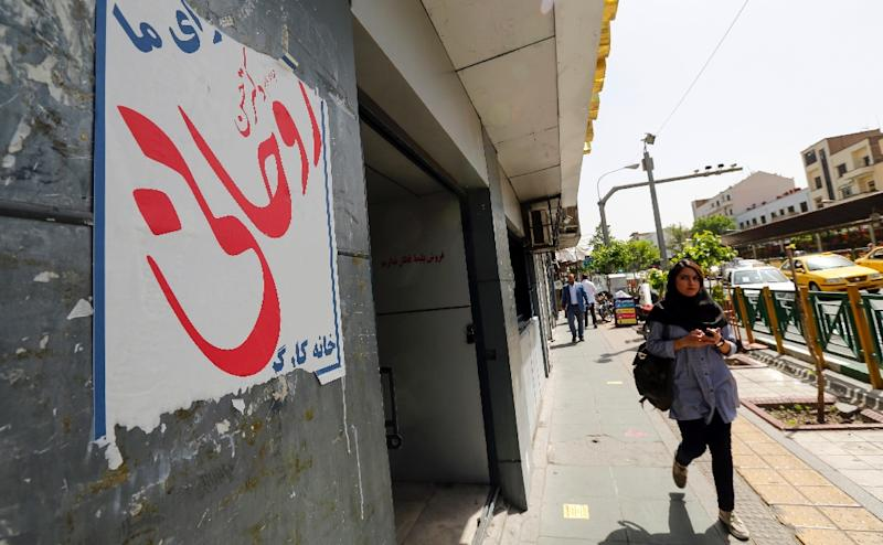An Iranian woman walks past election posters for President Hassan Rouhani, who is running for the re-election, in Tehran on April 23, 2017 (AFP Photo/ATTA KENARE)