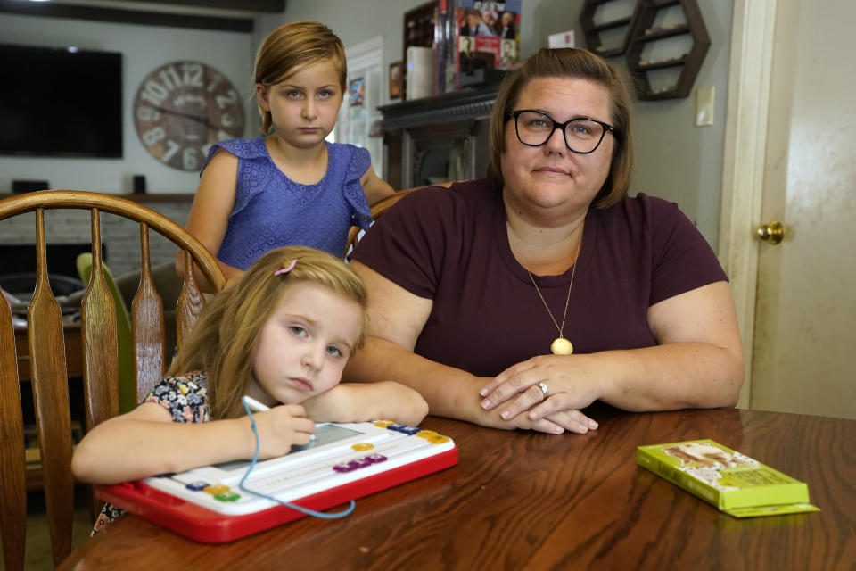 Kristin Goree and her daughters, Hazel, 5, left, and Evelyn 9, center pose for a photo at their home in Sacramento, Calif., Tuesday, Oct. 5, 2021. California schools have a few statewide requirements for how schools apply COVID rules for schools but leave most details up to the local districts, leading to a dizzying patchwork of approaches that Goree and many other parents say can be confusing and frustrating. Kirstin Goree felt she had no other choice but to send her two daughters back to in-person learning even though she does not trust the school's COVID protocols.(AP Photo/Rich Pedroncelli)