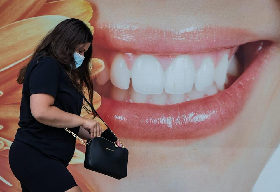 """<span class=""""caption"""">A woman walks past a photograph of a smiling woman outside a dental office, in Vancouver, B.C., Aug. 3, 2020. </span> <span class=""""attribution""""><span class=""""source"""">THE CANADIAN PRESS/Darryl Dyck</span></span>"""
