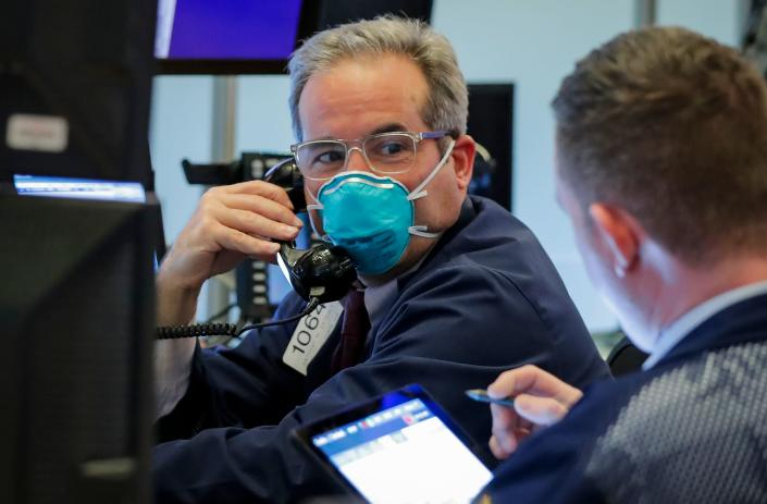 A trader wears a face mask on the floor of the New York Stock Exchange (NYSE) following traders testing positive for Coronavirus disease (COVID-19), in New York, U.S., March 19, 2020. REUTERS/Lucas Jackson