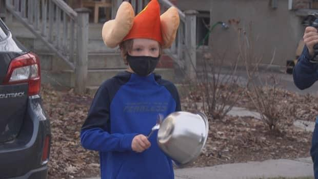 A child bangs a pot on Tweedsmuir Avenue in Ottawa's Westboro neighbourhood to show thanks for front-line workers. It's something the street's residents have done every day for the past year. (Andrew Lee/CBC - image credit)