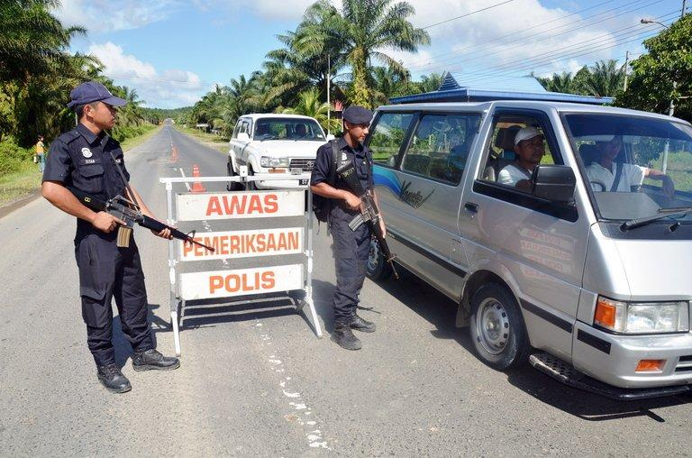 Two armed policemen man a security check post in a village of Bakapit near Lahad Datu, on the Malaysian island of Borneo on February 14, 2013. Malaysia's government said Thursday its security forces have surrounded dozens of Philippine gunmen in a remote area of Borneo island, and a report said the group is demanding the right to stay