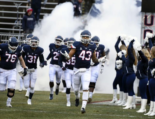 FILE - In this Nov. 24, 2018, file photo, Connecticut linebacker Darrian Beavers (43) leads his team onto the field before the start of an NCAA college football game against Temple in East Hartford, Conn. UConn football is on the road to independence and the American Athletic Conference is not feeling any pressure to replace the Huskies when they leave for the Big East. The University of Connecticut is set to announce later this week that it will be leaving the AAC and re-joining the Big East, which does not sponsor football, in 2020. (AP Photo/Stephen Dunn, File)