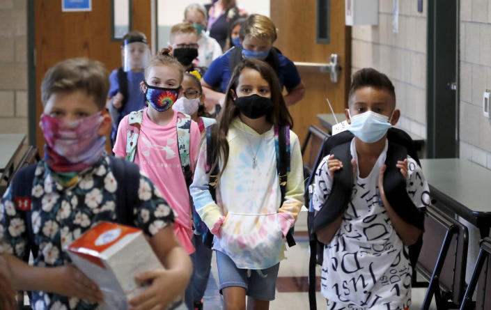 Wearing masks to prevent the spread of Covid, elementary school students walk to classes to begin their school day in Godley, Texas, on Aug. 5, 2020. (LM Otero / AP)