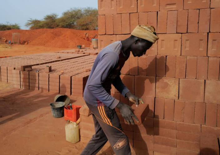 A worker carries a newly made brick at the Elementerre factory in Mbour
