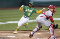 Oakland Athletics' Tony Kemp (5) slides home to score beside Los Angeles Angels catcher Max Stassi, right, during the third inning of a baseball game in Oakland, Calif., Monday, June 14, 2021. (AP Photo/John Hefti)