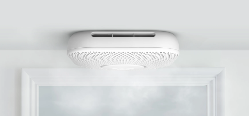 A Google Nest Protect smoke alarm installed on a ceiling.