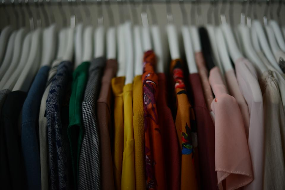 colorful blouses hanging on a white hangers in a row