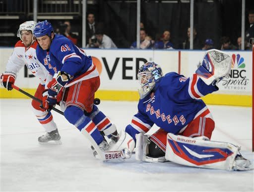 New York Rangers goaltender Henrik Lundquvist, right, of Sweden, makes a save as Rangers' Stu Bickel (41) holds off Washington Capitals' Troy Brouwer during the first period of an NHL hockey game on Saturday, April 7, 2012, at Madison Square Garden in New York. (AP Photo/Bill Kostroun)
