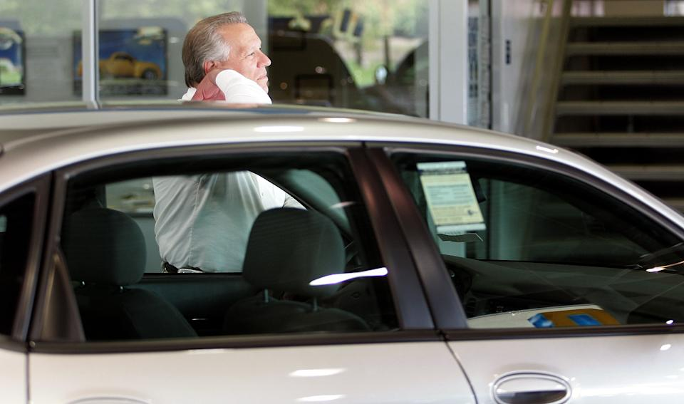 Sales and leasing consultant Ernie Alvinito looks out a window as he awaits a customer. (Photo: Tim Boyle/Getty Images)