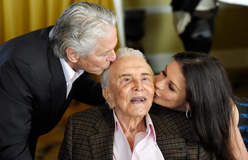 Actor Kirk Douglas, center, gets a kiss from his son Michael Douglas, left, and Michael's wife Catherine Zeta-Jones during his 100th birthday party at the Beverly Hills Hotel on Friday, Dec. 9. 2016, in Beverly Hills, Calif.