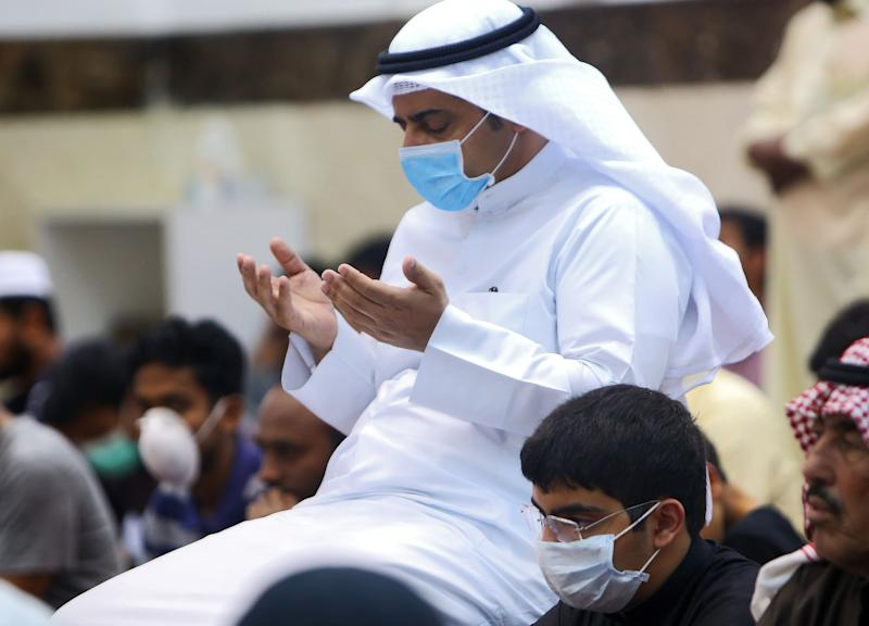 Muslim men wearing protective masks perform Friday prayers at a mosque in Kuwait City on February 28, 2020. - Kuwait's Ministry of Awqaf and Islamic Affairs set the Friday prayer sermon to not exceed 10 minutes, and to discuss precautions against COVID-19 coronavirus disease infections. Kuwait has recorded 43 coronavirus cases since its outbreak, the United Arab Emirates reported 13, while Bahrain has 33, and Oman is at four cases. Government institutions in the gulf country suspended the use of fingerprint recognition to clock in and out. (Photo by YASSER AL-ZAYYAT / AFP) (Photo by YASSER AL-ZAYYAT/AFP via Getty Images)