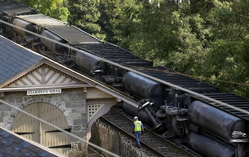An official walks alongside part of a CSX freight train that derailed overnight in Ellicott City, Md., Tuesday, Aug. 21, 2012. Authorities said two people not employed by the railroad were killed in the incident. (AP Photo/Patrick Semansky)
