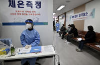 Nursing home workers, sitting at right, wait to receive the first dose of the AstraZeneca COVID-19 vaccine at a health care center in Seoul Friday, Feb. 26, 2021. South Korea on Friday administered its first available shots of coronavirus vaccines to people at long-term care facilities, launching a mass immunization campaign that health authorities hope will restore some level of normalcy by the end of the year. (Jung Yeon-je /Pool Photo via AP)