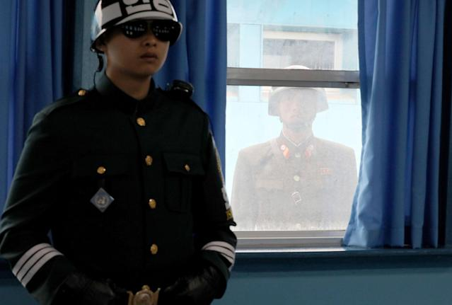 <p>A South Korean soldier, left, stands at the U.N. Command Military Armistice Commission meeting room as a North Korean soldier is seen through the window at the border village of Panmunjom in the Demilitarized Zone, South Korea, Wednesday, March 28, 2018. (Photo: Park Jin-hee/Newsis via AP) </p>